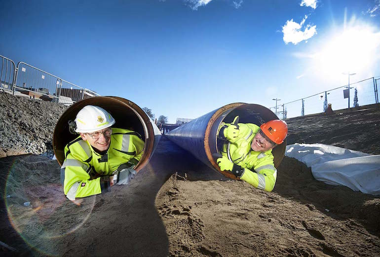 Anders Egelrud, CEO Fortum och Jon Karlung, CEO Bahnhof, closely inspecting pipes that'll carry excess heat from computer hardware into the city's central heating system.